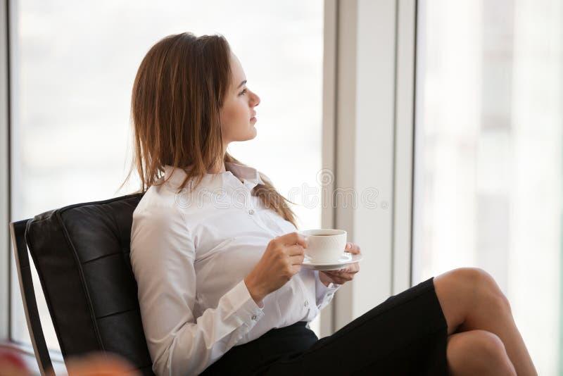 Empleado de sexo femenino confiado que come el café que sueña con el succe futuro fotos de archivo