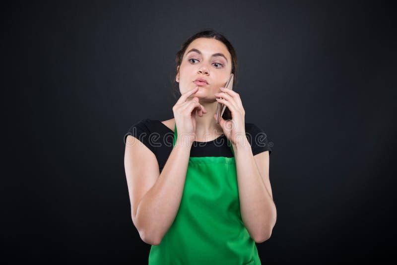 Empleado de sexo femenino del supermercado con el delantal verde foto de archivo libre de regalías