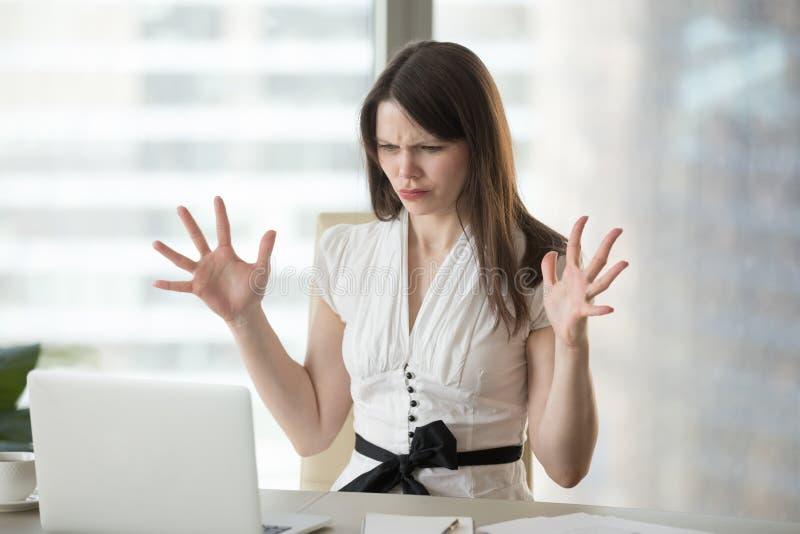 Empleado de sexo femenino enojado que tiene problemas de programación con el ordenador portátil foto de archivo libre de regalías