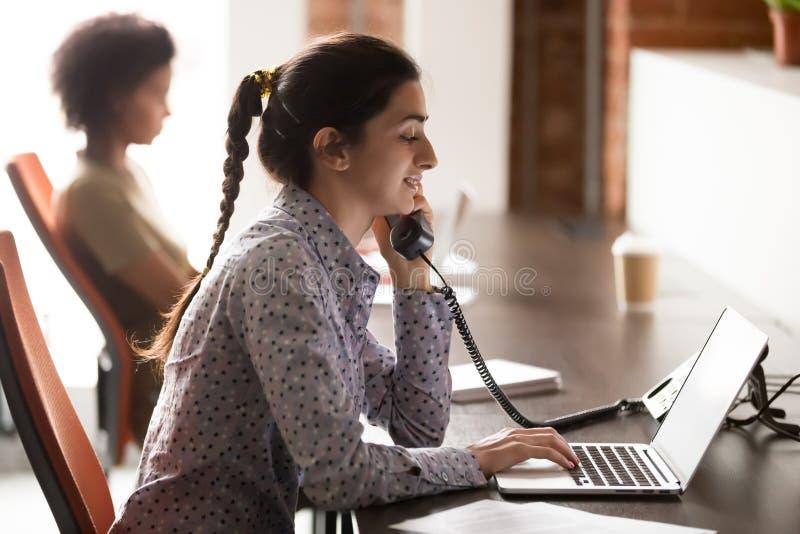 Empleado de sexo femenino indio consultar al cliente sobre el teléfono en oficina imagen de archivo libre de regalías