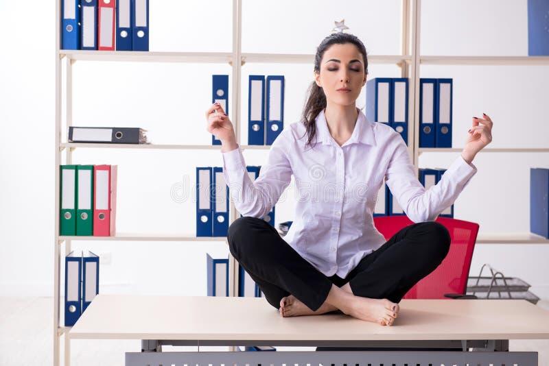 Empleado de sexo femenino joven que hace ejercicios en la oficina foto de archivo libre de regalías