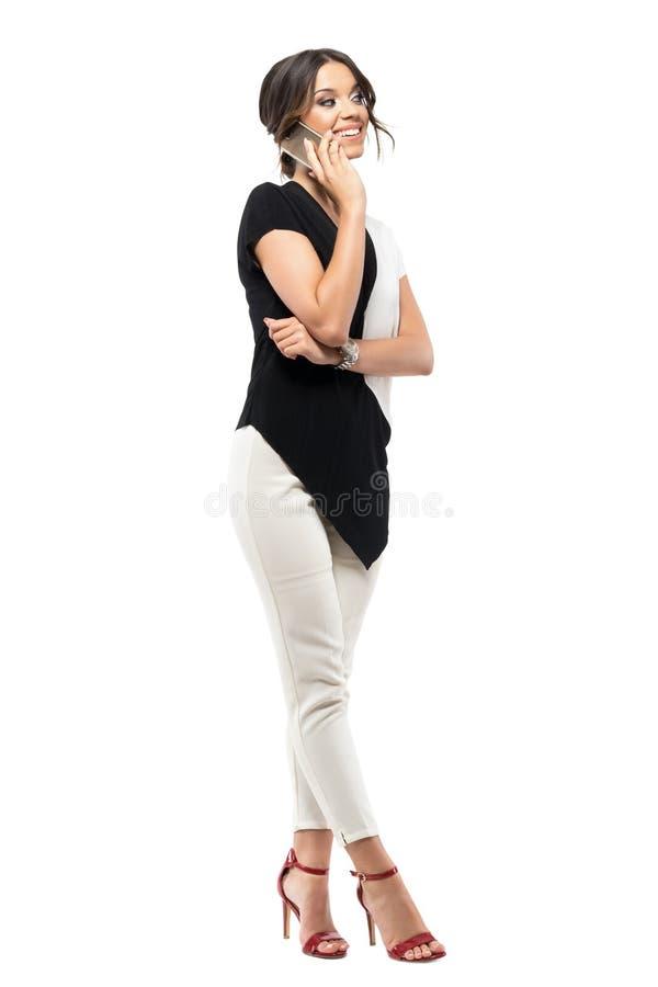 Empleado de sexo femenino joven que se relaja en la pausa que sonríe y que habla en el teléfono móvil fotografía de archivo libre de regalías