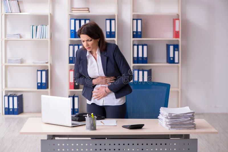 Empleado de sexo femenino de mediana edad que sufre en la oficina imágenes de archivo libres de regalías