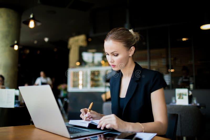 Empleado de sexo femenino que escribe un informe mensual en cuaderno del red-libro foto de archivo libre de regalías