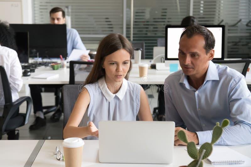 Empleado de sexo femenino que explica tarea del ordenador al workin masculino del compañero de trabajo imágenes de archivo libres de regalías