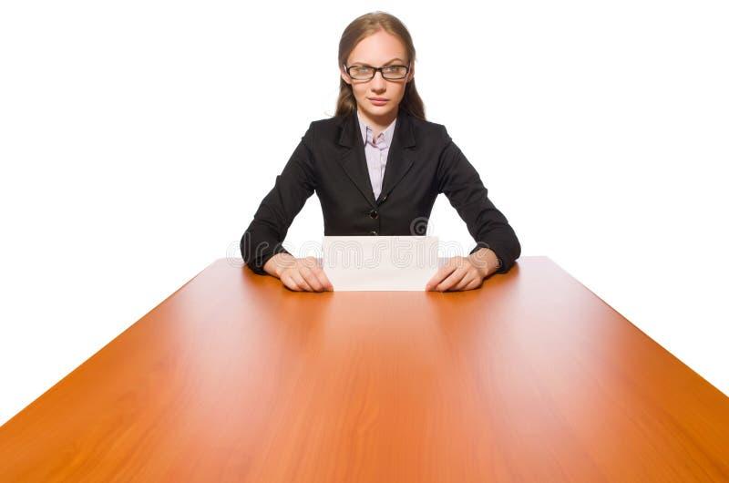 Empleado de sexo femenino que se sienta en la tabla larga aislada en blanco imagen de archivo