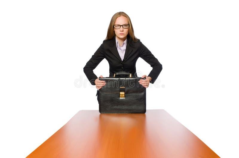 Empleado de sexo femenino que se sienta en la tabla larga aislada en blanco foto de archivo