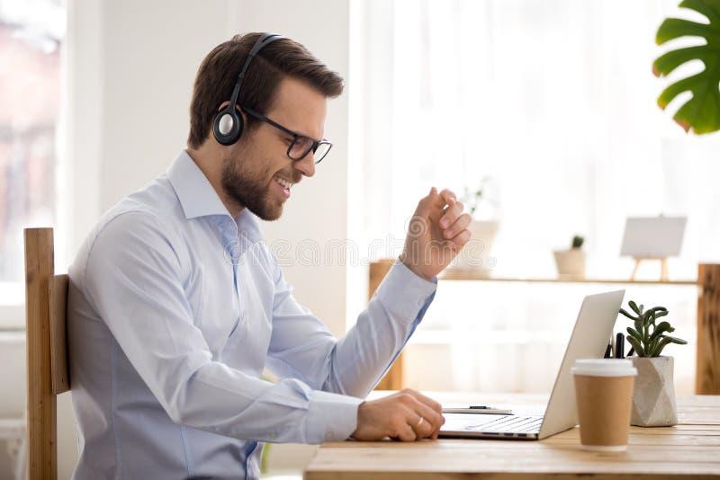 Empleado de sexo masculino feliz en auriculares escuchar la música en línea foto de archivo libre de regalías