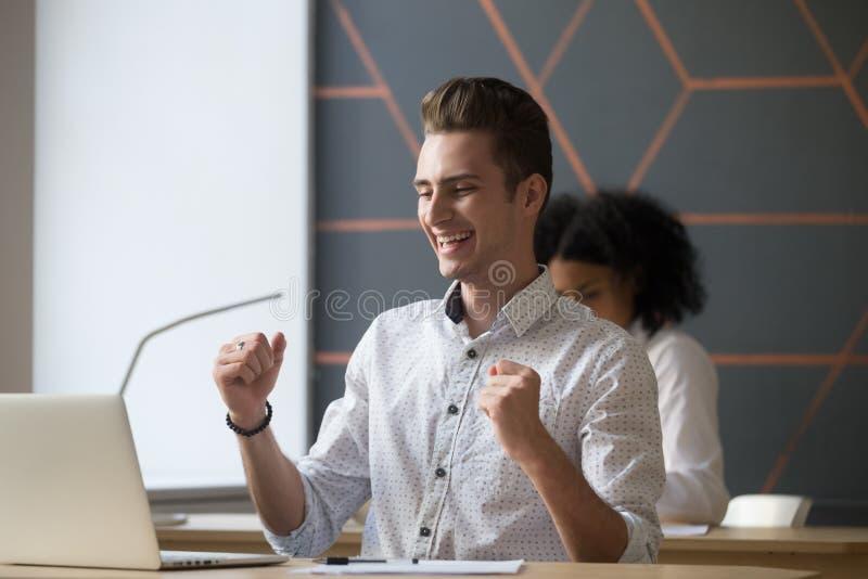 Empleado de sexo masculino feliz que celebra el buen resultado en línea que mira el la foto de archivo