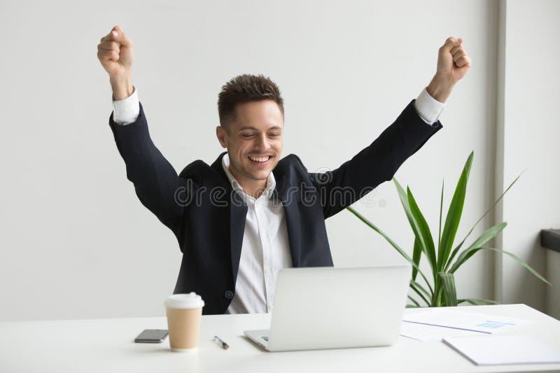 Empleado de sexo masculino feliz que celebra el buen resultado en línea que mira el la fotos de archivo libres de regalías
