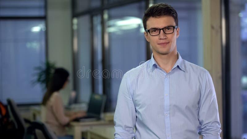 Empleado de sexo masculino hermoso en formalwear y lentes que miran la cámara, negocio fotos de archivo libres de regalías