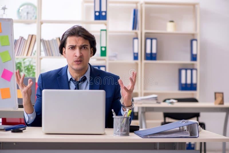 Empleado de sexo masculino joven infeliz con el trabajo excesivo foto de archivo libre de regalías