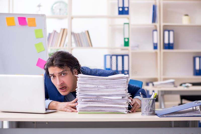 Empleado de sexo masculino joven infeliz con el trabajo excesivo fotografía de archivo libre de regalías