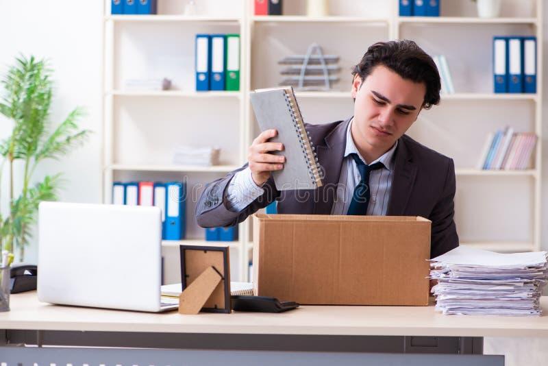 Empleado de sexo masculino joven que es encendido de su trabajo imagen de archivo libre de regalías