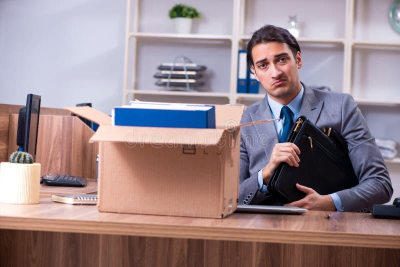 Empleado de sexo masculino joven que es encendido de su trabajo imagen de archivo