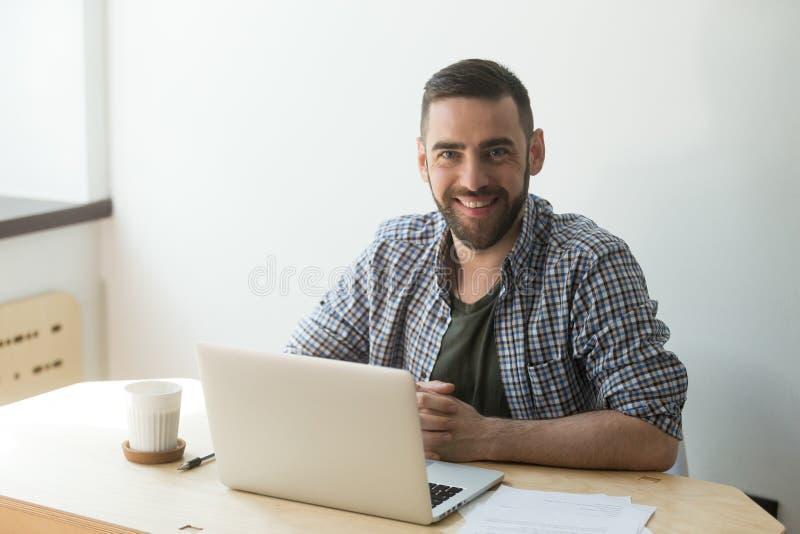 Empleado de sexo masculino que presenta para la foto en el escritorio del lugar de trabajo en corporat foto de archivo