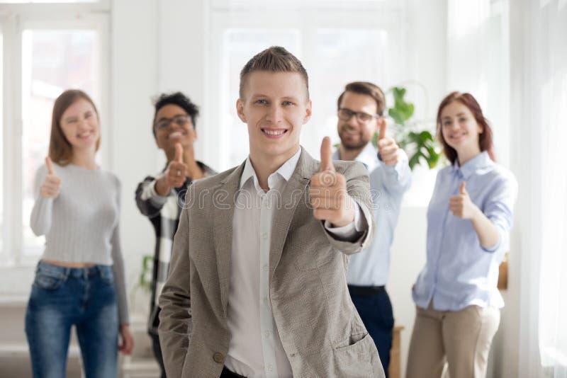 Empleado de sexo masculino sonriente con los pulgares diversos de la demostración del equipo para arriba fotografía de archivo