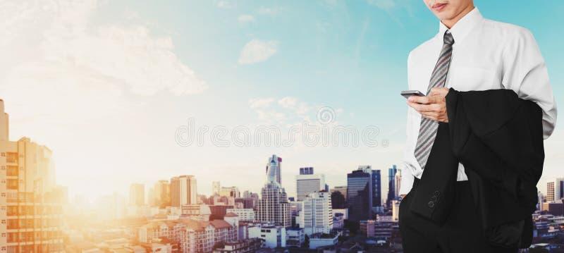Empleado del negocio que usa smartphone con la ciudad panorámica en fondo de la salida del sol fotografía de archivo libre de regalías