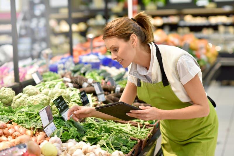 Empleado del supermercado en la sección vegetal imagen de archivo