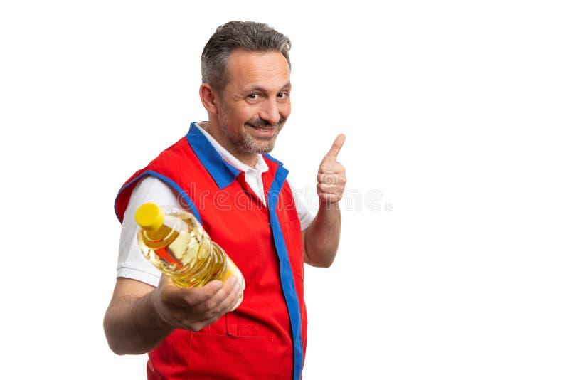 Empleado del supermercado que hace el pulgar encima del gesto a la botella de aceite fotos de archivo