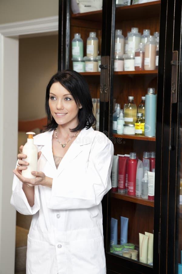 Empleado feliz del salón de belleza que sostiene productos cosméticos mientras que mira lejos foto de archivo