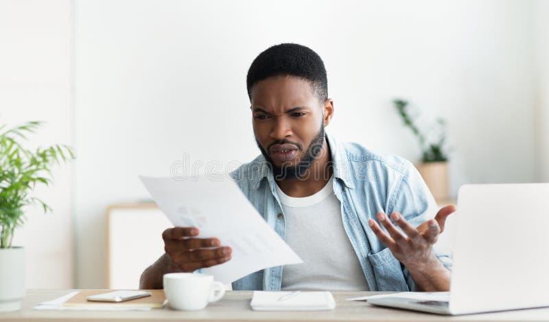 Empleado frustrado chocado por informe financiero de lectura de su compañía fotografía de archivo libre de regalías