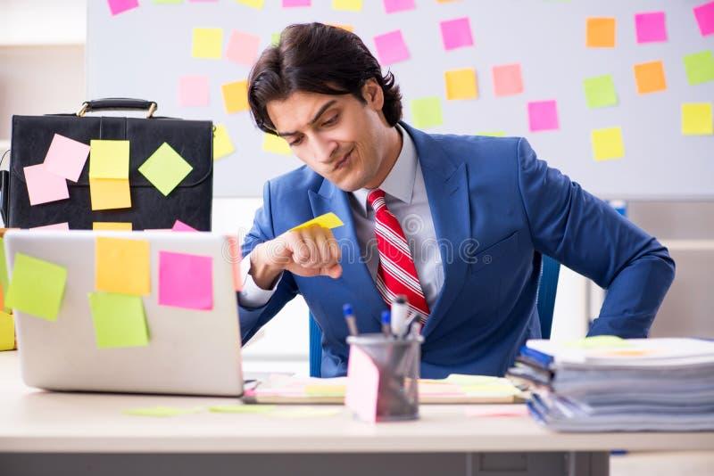 Empleado hermoso de sexo masculino joven en concepto de las prioridades que est? en conflicto imágenes de archivo libres de regalías