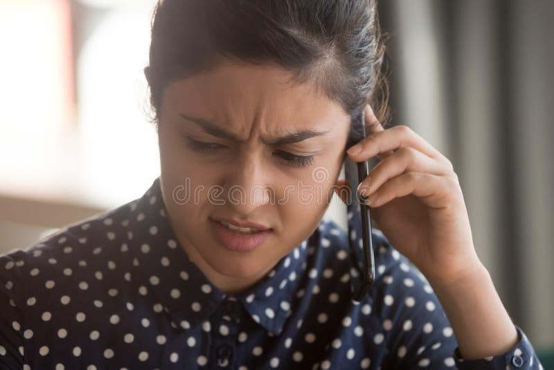 Empleado indio de sexo femenino que tiene conversaci?n desagradable del tel?fono m?vil foto de archivo libre de regalías