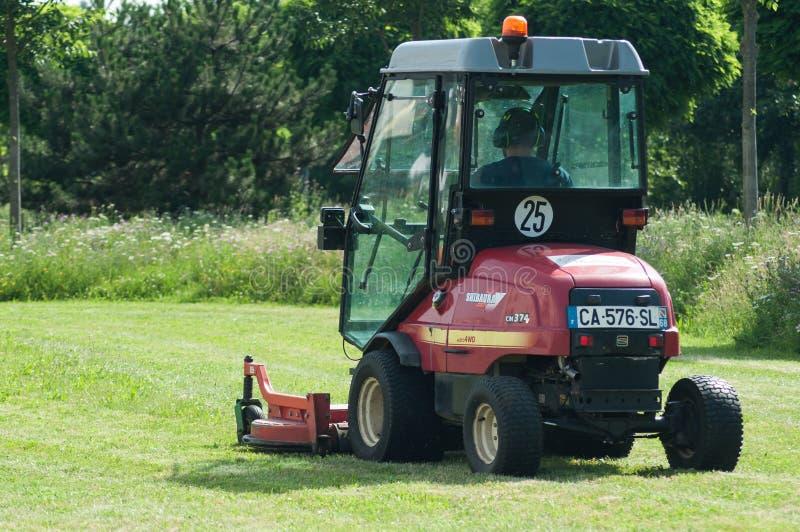 Empleado municipal que conduce el tractor y el cortacésped rojos, céspedes de los esquileos en parque urbano fotografía de archivo