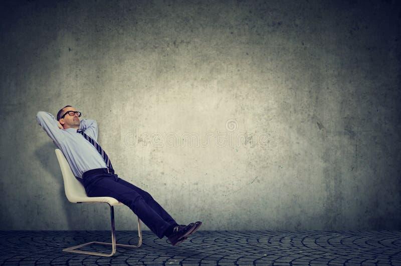 Empleado relajado que se sienta en silla imagen de archivo libre de regalías