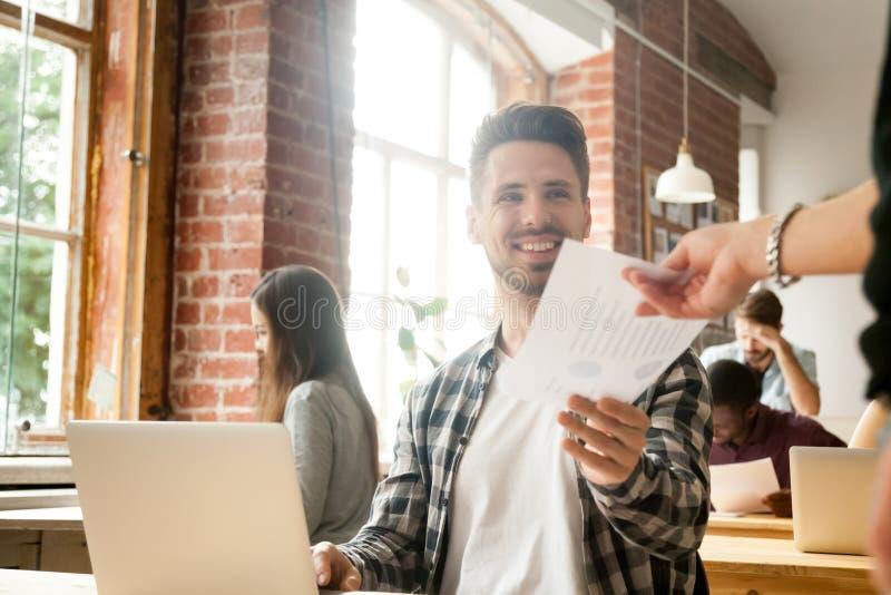 Empleado sonriente que da informe al ejecutivo satisfecho con el trabajo imagen de archivo