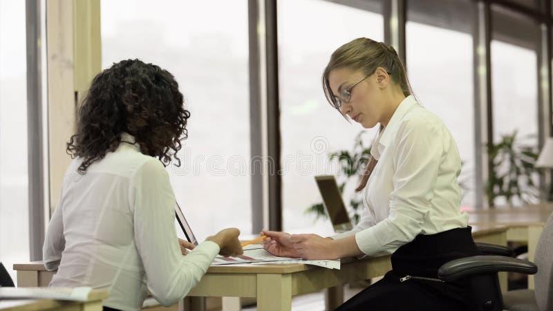 Empleados bastante de sexo femenino que comprueban los papeles, equipo de la oficina que trabaja en proyecto junto foto de archivo