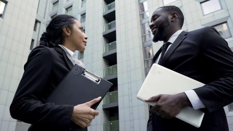 Empleados de la compañía que hablan cerca del edificio de oficinas, trabajo en equipo acertado en proyecto fotos de archivo libres de regalías