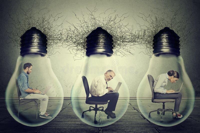 Empleados de la compañía que se sientan en fila dentro de la bombilla de la lámpara eléctrica usando el ordenador portátil fotografía de archivo libre de regalías