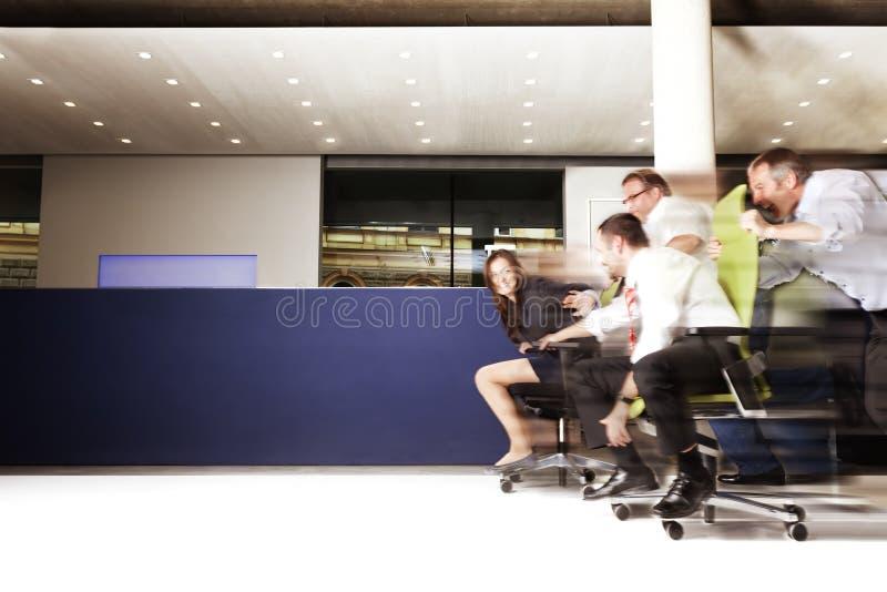 Empleados de oficina emocionados en una raza de la silla. imágenes de archivo libres de regalías