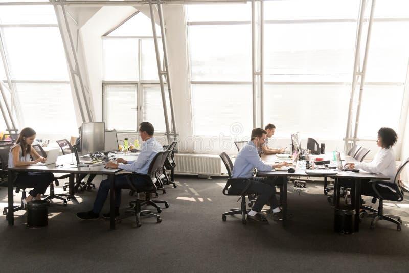 Empleados diversos centrados en el trabajo en las mesas en offic compartida imagenes de archivo
