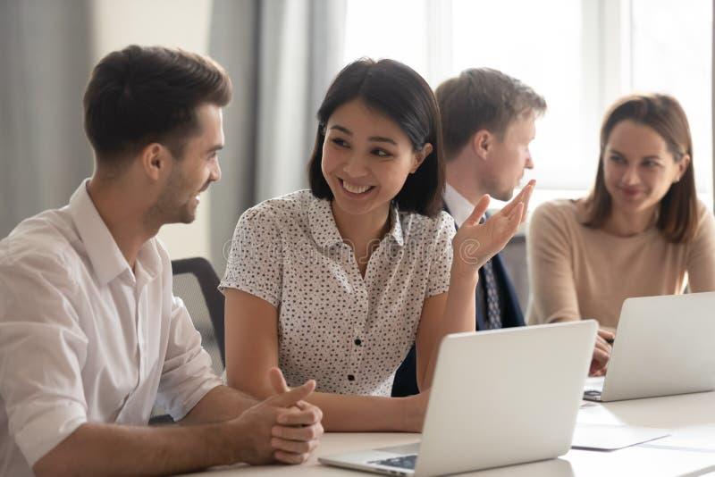 Empleados diversos felices que hablan el funcionamiento de risa así como los ordenadores portátiles de los compañeros de trabajo fotos de archivo