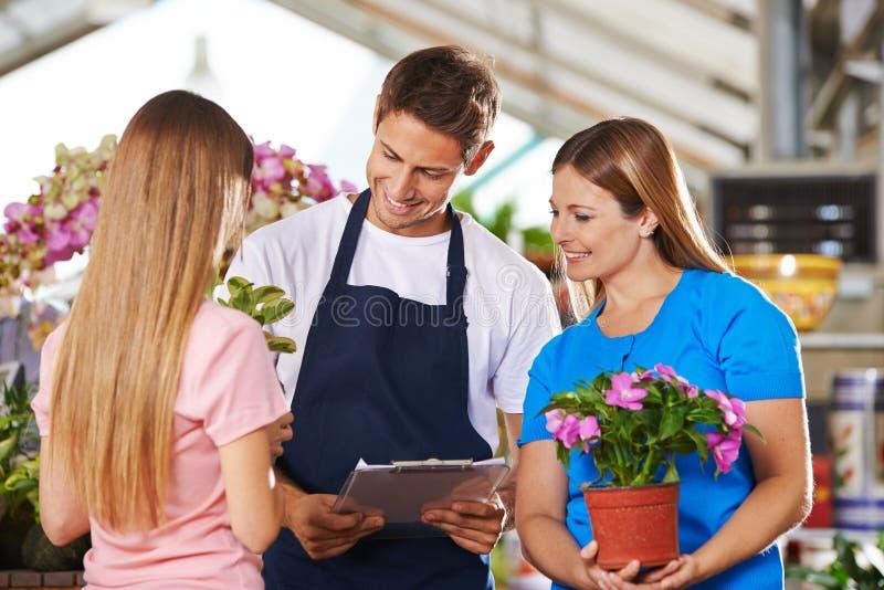 Empleados en la floristería con consejo de clientes fotografía de archivo libre de regalías