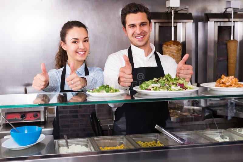 Empleados felices que trabajan con kebab foto de archivo libre de regalías