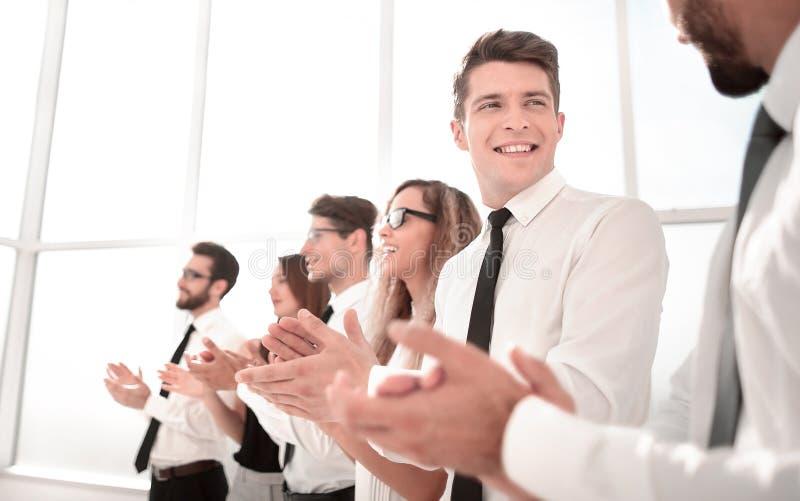 Empleados jovenes de la compañía una ovación de pie foto de archivo libre de regalías