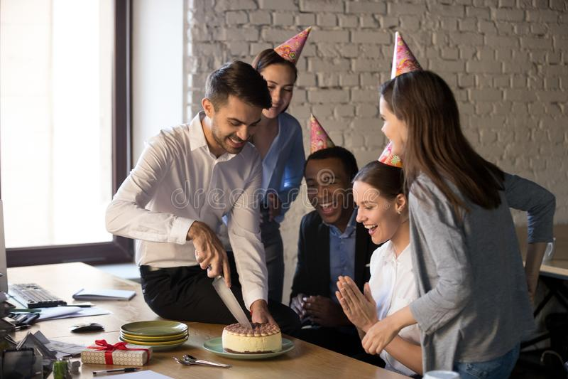 Empleados multi-étnicos amistosos que cortan la torta que celebra birthda fotografía de archivo