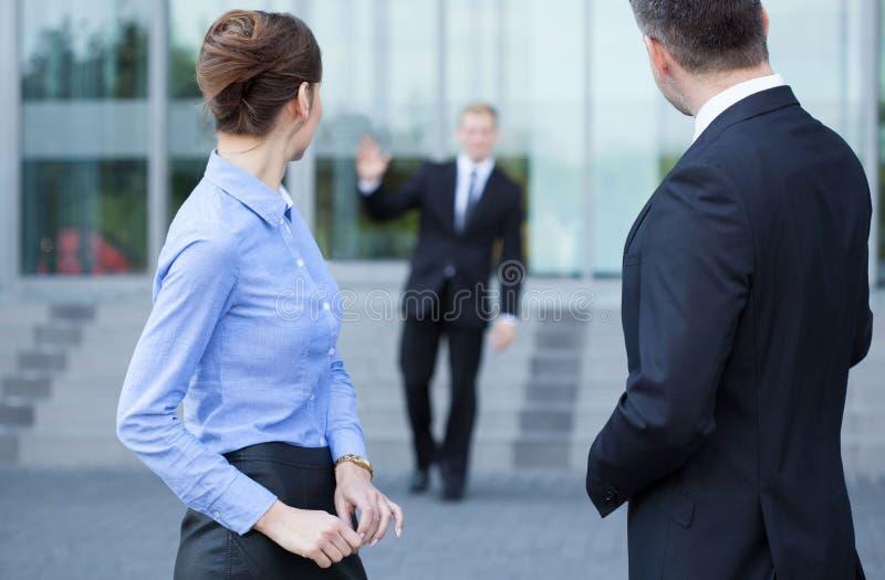 Empleados que hablan delante de centro de negocio foto de archivo