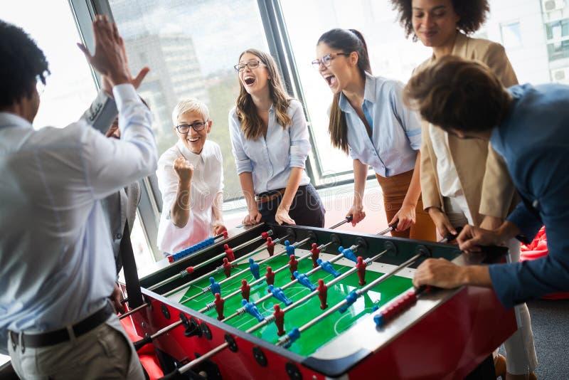 Empleados que juegan al juego interior del fútbol de la tabla en la oficina durante tiempo de la rotura imagenes de archivo