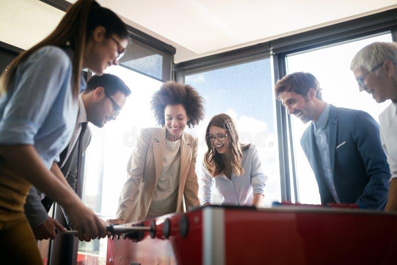 Empleados que juegan al juego interior del f?tbol de la tabla en la oficina durante tiempo de la rotura imagenes de archivo