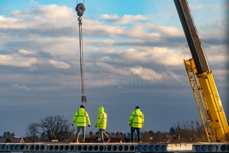 Empleados que trabajan en la construcción de un bloque de viviendas Construcciones en la construcción de la casa fotografía de archivo