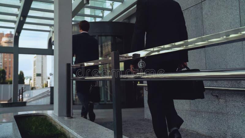 Empleados que vienen trabajar temprano por la mañana, hombres de negocios, carrera del edificio fotos de archivo libres de regalías