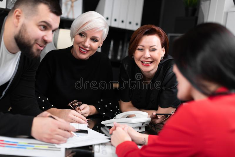 Empleados sonrientes que hablan en lugar de trabajo fotos de archivo libres de regalías