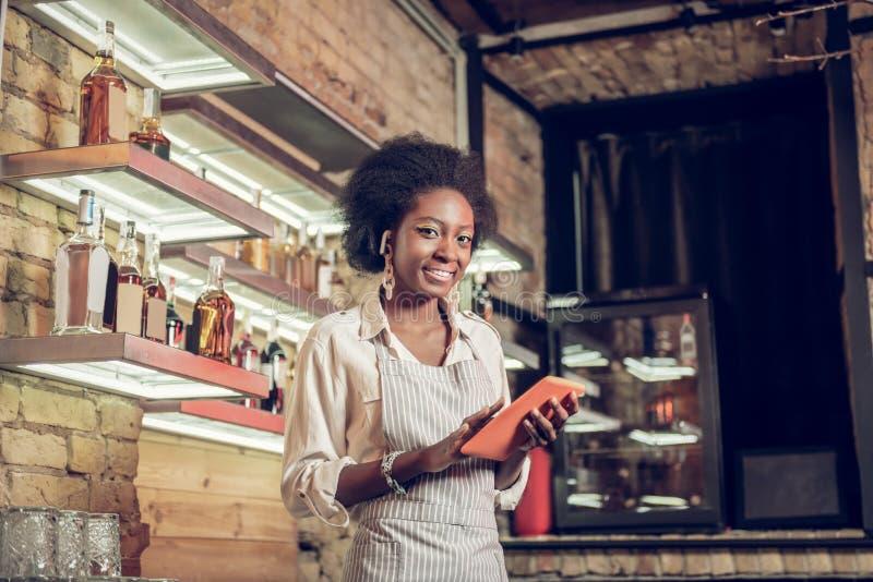 Employé afro-américain de charme de barre complétant la forme d'ordre de comprimé photo stock