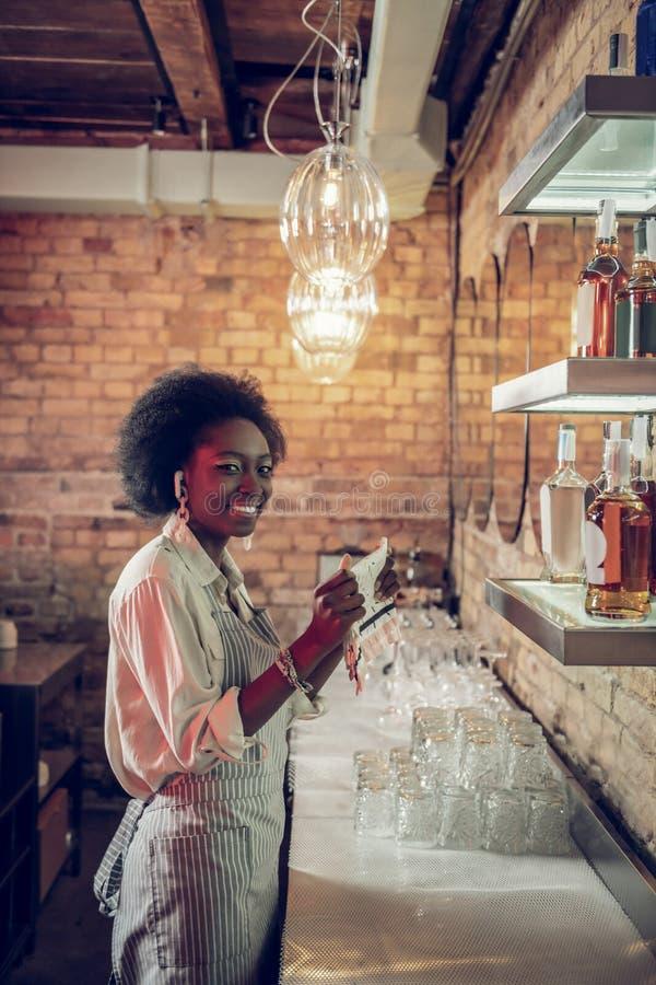 employé afro-américain enchantant de lancement de barre de Jeune-adulte tenant des serviettes à la barre images stock