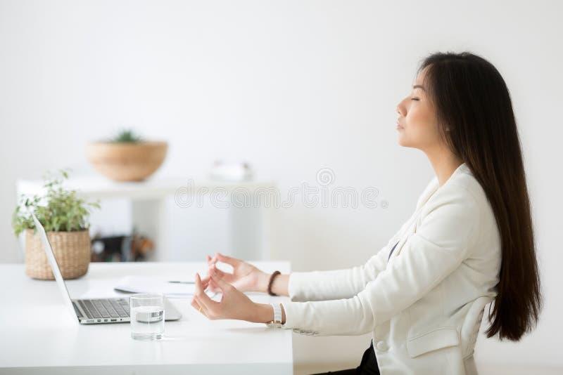 Employé asiatique calme méditant dans le bureau soulageant des contraintes du travail photo libre de droits